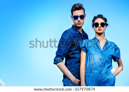 Portrait of a modern young people wearing jeans clothes and sunglasses over blue sky. Fashion shot. - stock photo