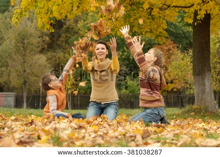 Portrait of a mom with kids in autumn park
