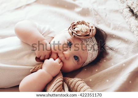 Portrait of a 4 month cute baby girl wearing lace flower headband and lying down on a bed with polka dot brown bedding - stock photo