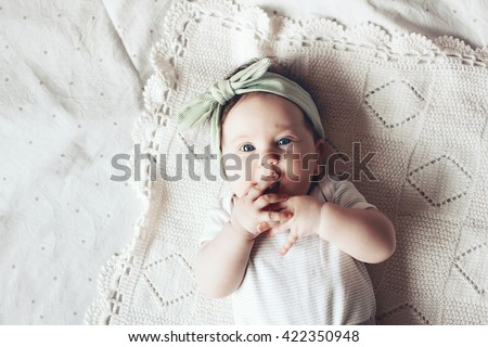 Portrait of a 4 month cute baby girl wearing lace flower headband and lying down on a crochet blanket - stock photo