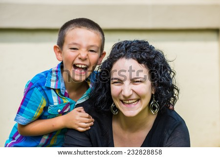 Portrait of a monther and her son outside on the lawn on a nice summer day, both looking at the camera and laughing happily. Son slightly behind mother with his hand on her shoulder.