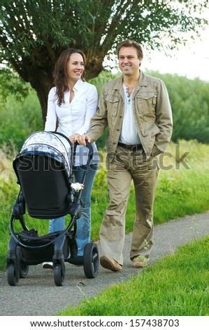 Portrait of a mother and father walking outdoors with baby stroller