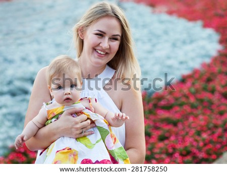 Portrait of a mother and her baby enjoy the summer day - stock photo