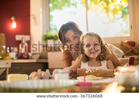Portrait of a mother and her four years old blonde daughter cooking in a kitchen. They are looking at camera, working on a pasty with a rolling pin on a table full of ingredients. shot with flare - stock photo