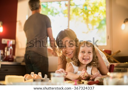 Portrait of a mother and her four years old blonde daughter cooking in a luminous kitchen. They are looking at camera, posing on a table full of ingredients. The dad is doing the dishes.