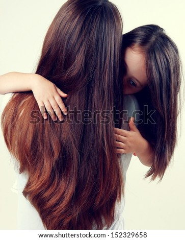 Portrait of a mother and little daughter with long beautiful hair - stock photo