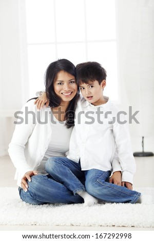 Portrait of a mother and son embracing in living room and smiling - stock photo