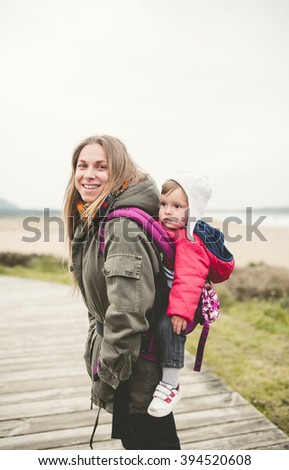 Portrait of a mother carrying her child in a backpack outdoors in a cloudy day