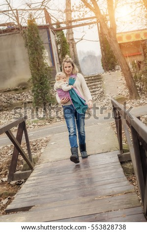 Portrait of a mother carrying her little baby in a baby carrier scurf in the park