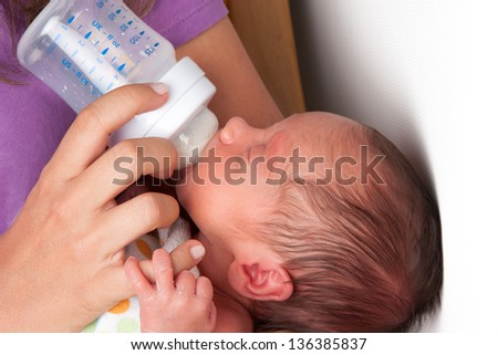 Portrait of a Mother Feeding Her Sweet Newborn Baby