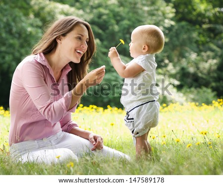 Portrait of a mother giving child flower in the park - stock photo
