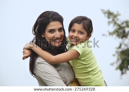 Portrait of a mother holding her daughter - stock photo