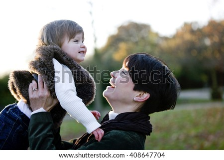 Portrait of a mother holding her daughter in the park, laughing - stock photo