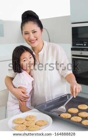 Portrait of a mother hugging her daughter while preparing cookies in the kitchen at home