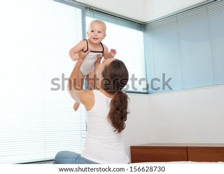 Portrait of a mother lifting up and playing with a happy baby