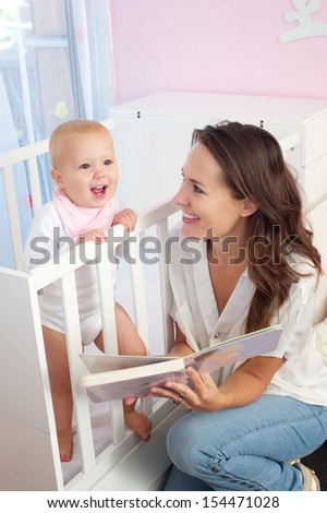 Portrait of a mother reading book to baby - stock photo
