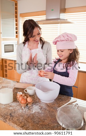 Portrait of a mother teaching her daughter how to bake in a kitchen - stock photo