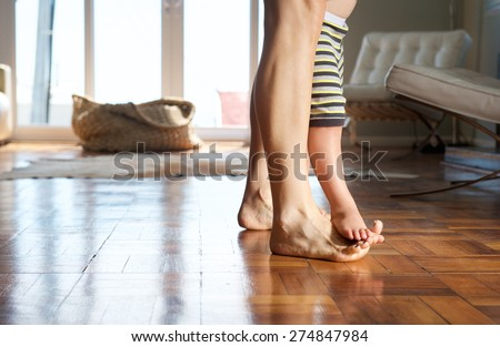 Portrait of a mother walking at home with child standing on her feet - stock photo