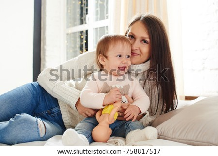 Portrait of a mother with a little baby girl on white bed in home interior