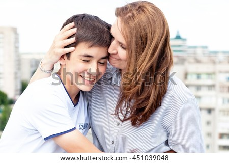 Portrait of a mother with her son teenager. Tenderness, love, multinational family - stock photo