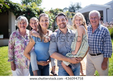 Portrait of a multi-generation family in the garden on a sunny day - stock photo