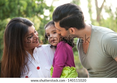 portrait of a multi racial family, father kissing the daughter. Indian family of three. - stock photo