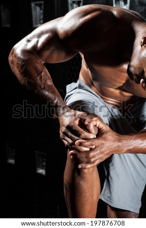 Portrait of a muscle fitness man reaching for his knee in pain - stock photo