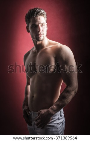 Portrait of a muscular and confident young man against a red background. Attractive male model. - stock photo