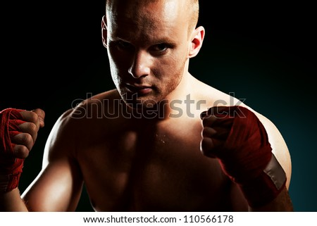 Portrait of a muscular boxer in red gloves posing at studio.