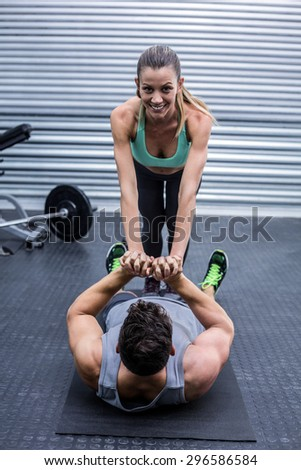 Portrait of a muscular couple doing core exercises - stock photo