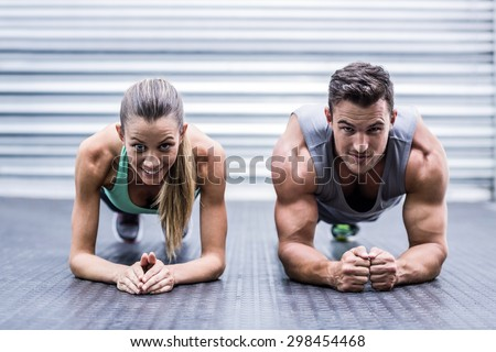 Portrait of a muscular couple doing planking exercises - stock photo