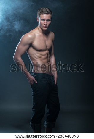 Portrait of a muscular male model against dark background with smoke. - stock photo