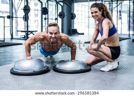 Portrait of a muscular man doing bosu ball push ups - stock photo