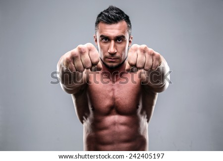 Portrait of a muscular man hitting into camera