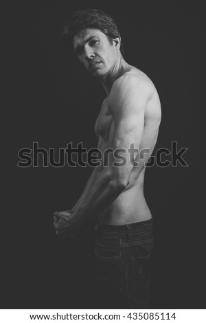 Portrait of a muscular man in a studio.  He is very lean and muscular, his abs very defined.  Fade has been used to make the image more atmospheric in feel.