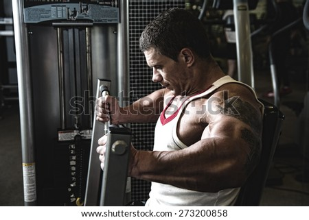Portrait of a muscular man in the gym. A strong man bodybuilder on a simulator shakes muscles. fitness training - stock photo