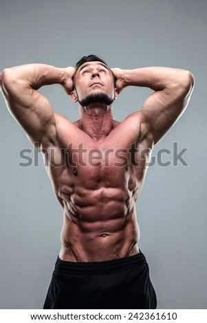 Portrait of a muscular man looking up over gray background