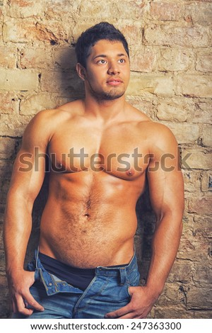 Portrait of a muscular man posing against old wall
