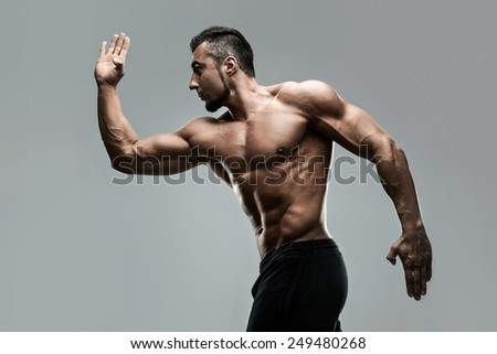 Portrait of a muscular man posing over gray background - stock photo