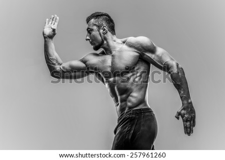 Portrait of a muscular man posing over gray background. HDR monochrome - stock photo