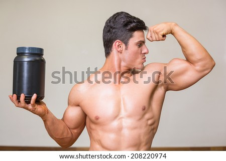 Portrait of a muscular man posing with nutritional supplement in gym - stock photo