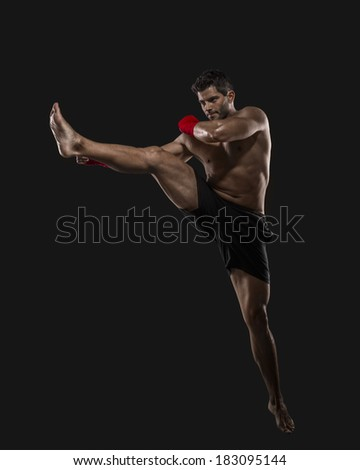 Portrait of a muscular man practicing body combat against a dark background - stock photo