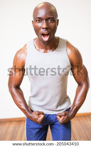 Portrait of a muscular man shouting while flexing muscles in gym - stock photo