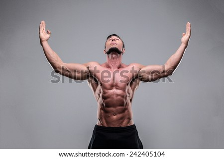 Portrait of a muscular man with raised hands up over gray background