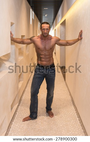 Portrait Of A Muscular Mature Man In The Modern Corridor Where He Poses - stock photo