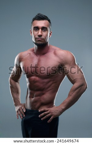 Portrait of a muscular sportsman posing over gray background - stock photo