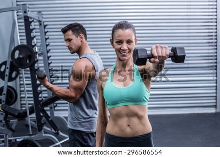 Portrait of a muscular woman lifting dumbbells - stock photo