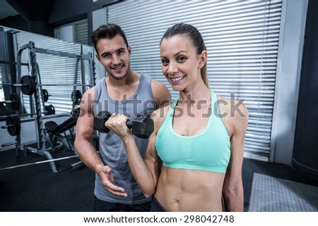 Portrait of a muscular woman lifting dumbbells helped by a coach - stock photo