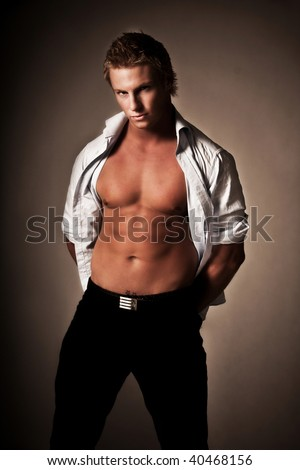 portrait of a muscular young man with  his shirt open - stock photo