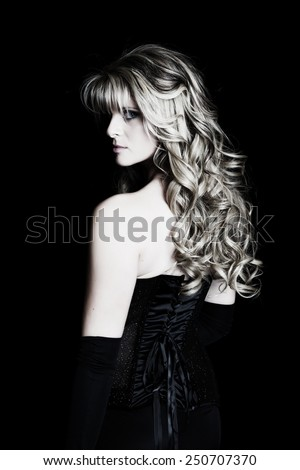 Portrait of a mysterious young woman dressed in formal wear.  Black background. - stock photo